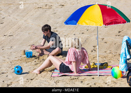 Bournemouth, Dorset, UK. 19th April 2018. UK weather: lovely warm sunny day at Bournemouth beaches with clear blue skies and unbroken sunshine, as visitors head to the seaside to enjoy the warmest day of the year so far. Couple relaxing on the beach under colourful parasol. Credit: Carolyn Jenkins/Alamy Live News - Stock Photo