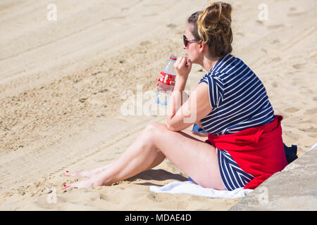 Bournemouth, Dorset, UK. 19th April 2018. UK weather: lovely warm sunny day at Bournemouth beaches with clear blue skies and unbroken sunshine, as visitors head to the seaside to enjoy the warmest day of the year so far. Young woman sitting on beach holding empty Coca-Cola bottle. Credit: Carolyn Jenkins/Alamy Live News - Stock Photo