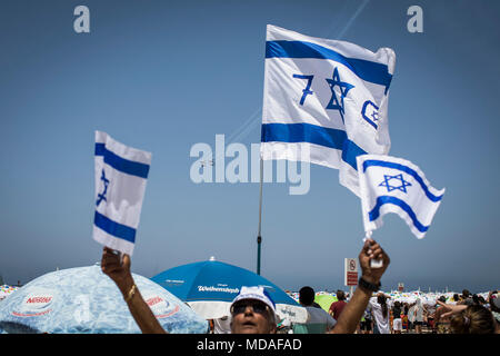 Tel Aviv, Israel. 19th Apr, 2018. A man waves Israeli flags as he watches a military air show during the celebrations marking the 70th anniversary of Israel's independence, in Tel Aviv, Israel, 19 April 2018. The day marks when David Ben-Gurion, the Executive Head of the World Zionist Organization, declared independence on the ashes of the Holocaust and the end of the British Mandate over Palestine in 1948. Credit: Ilia Yefimovich/dpa/Alamy Live News - Stock Photo