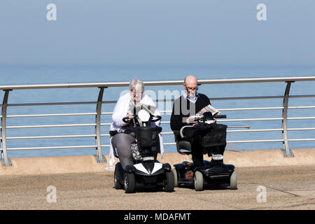 Sunny Day at the Seaside, Blackpool, Lancashire. 19th April 2018.  UK Weather.  An elderly couple sit in their mobility scooters sit in the sunshine reading the daily newspaper on Blackpool seafront in Lancashire.  Credit: Cernan Elias/Alamy Live News - Stock Photo