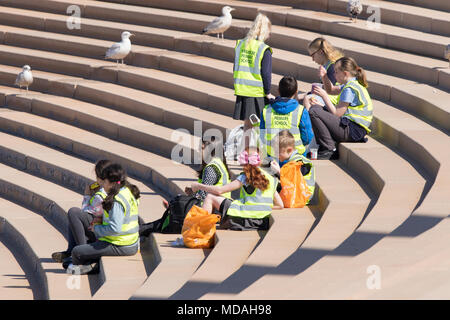 A group of young schoolchildren wearing hi viz vests for a school day outing in Blackpool Lancashire. - Stock Photo