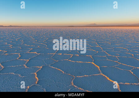 Sunset in the Uyuni salt flat (Salar de Uyuni) with the last sun rays shining on the mineral hexagon formations, Bolivia, South America. - Stock Photo