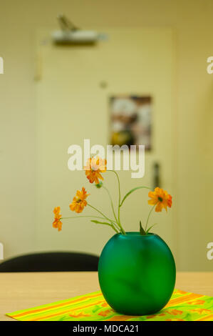 Hamburg, Germany - November 25, 2014: Green vase with synthetic orange  flowers on table in dull restroom. - Stock Photo