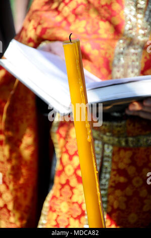 isolated yellow candle in front of orthodox priest holding a Bible, close up, outdoor celebration of Easter - Stock Photo