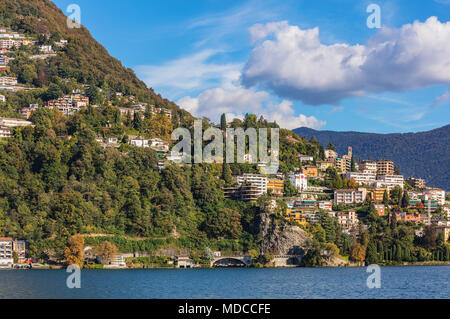 Buildings on the foot of the Monte Bre mountain in Switzerland, view from the city of Lugano in the Swiss canton of Ticino. - Stock Photo