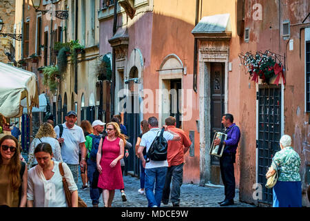 ROME, ITALY - MAY 17, 2017: A street artist playing his instrument and tourists walking down the street in Trastevere, Rome, Italy. - Stock Photo