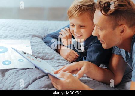 Nice handsome man teaching his son - Stock Photo