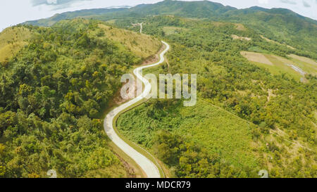 A long and winding road passing through green hills. Busuanga island. Coron. Aerial view. Philippines. - Stock Photo