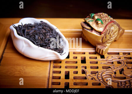 Dry black tea in a white bowl on a wooden board close-up. Tea cerimony. - Stock Photo
