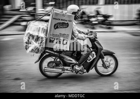 Motion blur motorcyclist carrying products on back of his bike, Hue Vietnam, south east asia - Stock Photo