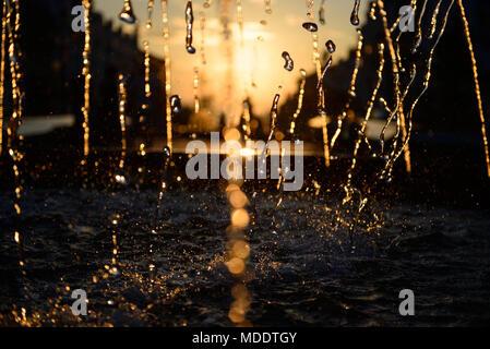 Water blurred splash in sunset light background - Stock Photo