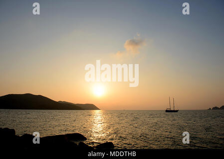 Lonely yacht in the sea sunset background - Stock Photo