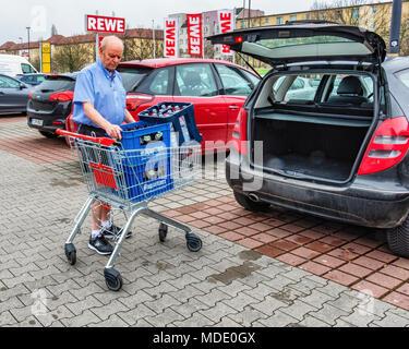 Berlin, Germany. Elderly senior man returning empty bottles to supermarket. Bottle recycling,recycles bottles,pfand deposit system - Stock Photo