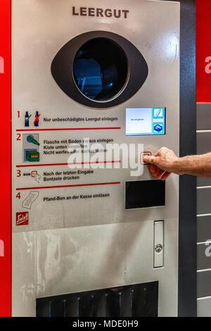 Berlin, Germany. Elderly senior man returning empty bottles to supermarket. Bottle recycling,recycles bottles.pfand deposit system - Stock Photo