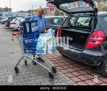 Berlin, Germany. Elderly senior man loading car boot with shopping  at Rewe supermarket - Stock Photo