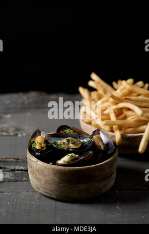 moules-frites, mussels and fries typical of Belgium, on a rustic wooden table, against a black background, with some blank space on top - Stock Photo