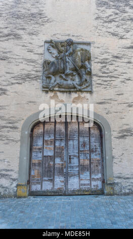 old handmade medieval wooden gate with a commemorative town seal above in an idyllic small European village - Stock Photo