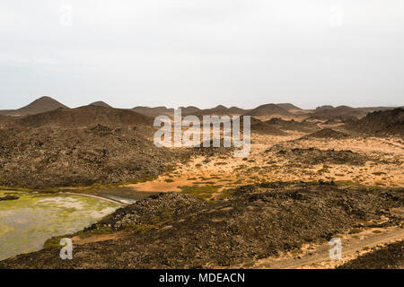 A small brackish water lake on the Isla de Lobos in Fuerteventura, Spain with the typical moon like volcanic landscape of the island. - Stock Photo