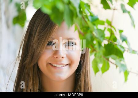 Only teens females face adult girl smiling at camera outdoors under tree branch happy happiness positive feeling enthusiastic smile - Stock Photo