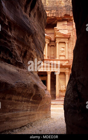 The Treasury viewed between Al Siq canyon walls of Petra, Jordan - Stock Photo