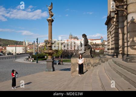 PRAGUE, CZECH REPUBLIC - April 14, 2018: Two young Japanese tourists take pfoto by Rudolfinum near Prague castle. - Stock Photo