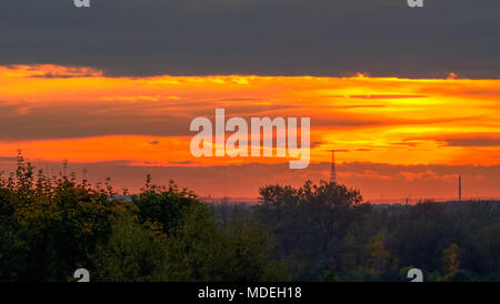 Magical energetic orange sunset with the Gliwice Radio Tower in the background in Zabrze, Silesia, Poland. - Stock Photo