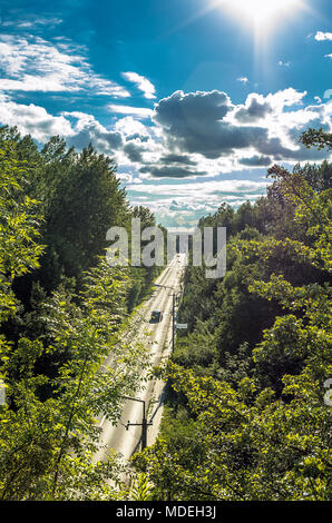 Road among forest with blue, cloudy sky and sun in the frame. Zabrze, Silesian Upland, Poland. - Stock Photo