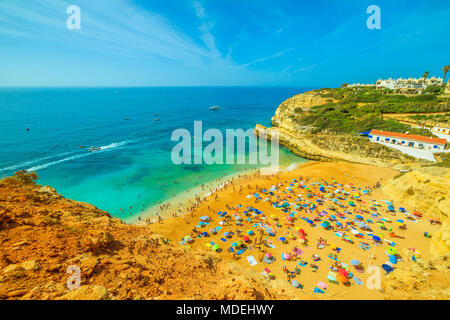 Aerial view of golden-colored cliffs of Praia de Benagil, Algarve near Lagoa, Portugal, Europe. Tourists sunbathing in famous Benagil beach known for an impressive cave, known as Algar de Benagil. - Stock Photo