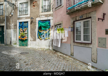 view of a typical narrow street in the historic center of Lisbon, Portugal - Stock Photo