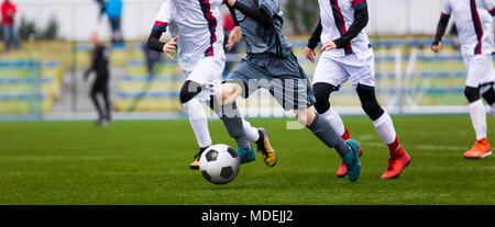 Junior Football Match. Soccer Game For Youth Players. Boys Playing Soccer Match on Football Pitch. Football Stadium and Grassy Field in the Background - Stock Photo