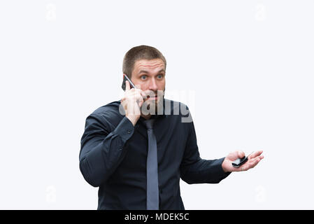 Bearded man emotionally talking on the phone near the car - Stock Photo