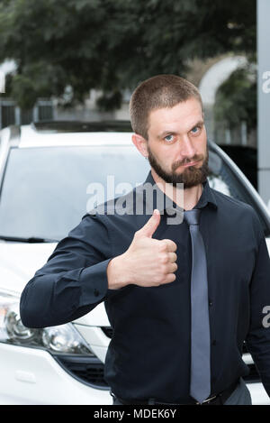 Bearded man with earring in the ear near the car shows a gesture - Stock Photo