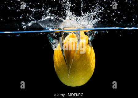 Lemon falling into the water and splashing drops on black background - Stock Photo