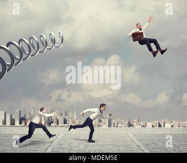 business challenge, businessman take advantage using huge metal spring - Stock Photo