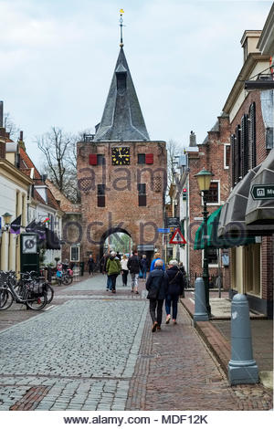 People stroll through the Vischpoort, a defensive tower built in the early 15th century; the passageway added in 1592 leads to the Elburg harbor. - Stock Photo