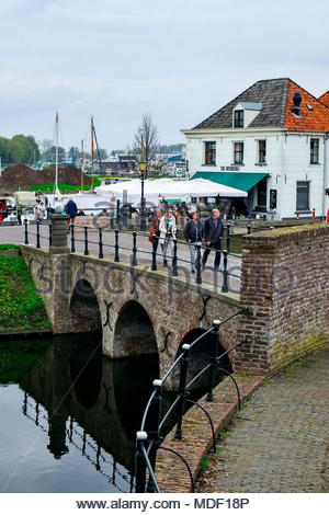 People cross the bridge on Havenstraat that leads to the old fortress city of Elburg as others enjoy lunch at De Herberg restaurant beside the harbor. - Stock Photo
