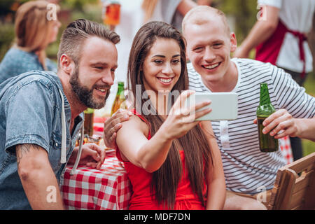 Happy friends taking a selfie while having a garden party - Stock Photo