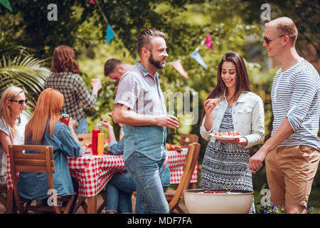 Student friends talking over a grill during a garden party in the summer - Stock Photo