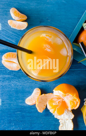 refreshing cocktail with tangerines, juice and ice in glass on a white wooden background, alcoholic drink, copy space - Stock Photo