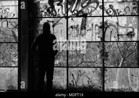 Man against glass wall broken windows in abandoned building. Black and white. - Stock Photo
