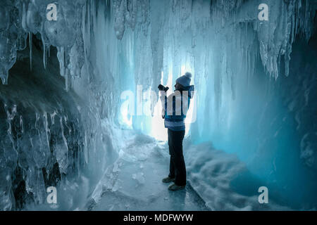 Woman standing in an ice cave taking a photo,Irkutsk Oblast,Siberia,Russia - Stock Photo