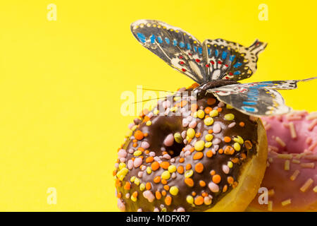 Sprinkled Pink and chokolate Donut. Frosted sprinkled donuts with butterfly on yellow background. Copy space at the left - Stock Photo