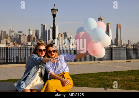 New York city urban women enjoying view of downtown Manhattan skyline. Fashionable girls with balloons, summer travel in USA - Stock Photo