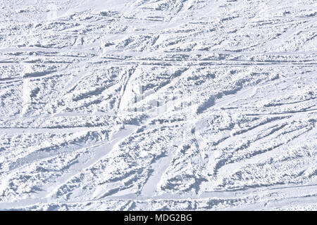 Ski slope with traces of skis on a sunny day. Background, texture. - Stock Photo
