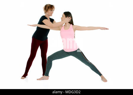 Yoga teacher shows how to put a young white girl in the Yoga position Warrior Pose, on sanskrit Virabradasana. - Stock Photo