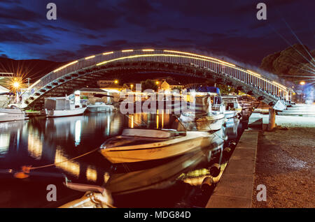 Arched bridge for pedestrians in Trogir, Croatia, Unesco. Night scene. Travel destination. Boats in the port. Yellow photo filter. - Stock Photo
