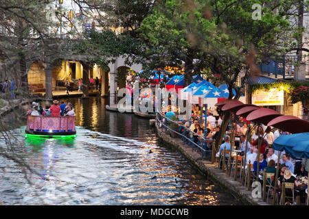 San Antonio River Walk -  - A tourist boat on the San Antonio river passing restaurants at dusk; the San Antonio Riverwalk, San Antonio Texas USA - Stock Photo