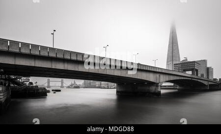 London Bridge and The Shard fade behind the foggy mist. - Stock Photo