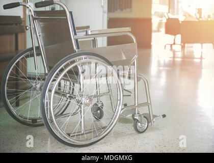 Empty wheelchair parked in hospital hallway with light hope concept - Stock Photo