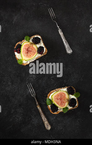 Seeded wholemeal bread toasts spread with creamy cheese, figs, blackberries and songino leaves. Top view. - Stock Photo